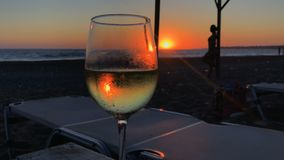 Glass with wine against silhouette of girl and sunset. Wineglass with white whine atsna at the table against red beautiful sea . Silhouette of girl is posing at stock video footage