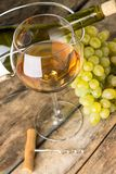 Wineglass with white wine, botlle, corkscrew and cluster of grapes around on wood background Stock Photo