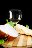 Wineglass of white wine cheese and ham Stock Photos