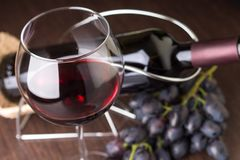 Wineglass with wine with grapes and bottle at background Royalty Free Stock Images