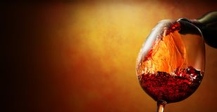 Wineglass with wine. Pouring from bottle on orange background royalty free stock photos