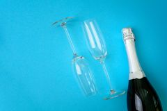 Wineglasses and bottle of champagne lying on blue paper background. New Year celebration concept. Top view. Flat lay stock image