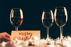 Wineglasses and christmas decorations. Three glasses with red wine on wooden table with fairylights, candles and merry christmas card Royalty Free Stock Image