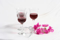 Wineglasses with flowers. Wineglasses and a pink flowers on a white surface Royalty Free Stock Image