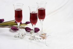 Wineglasses with Flowers. Wineglasses and artificial flowers on a white surface stock photo