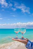 wineglasses in a man's hand on the white sandy beach Stock Photography
