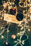 Wineglasses and merry christmas card. Two glasses with red wine on wooden table with fairylights, candles and merry christmas card Stock Photography