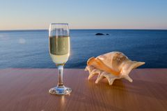 Wineglasses near by beautiful seashell on the wooden table, on the smooth sea landscape Royalty Free Stock Photo