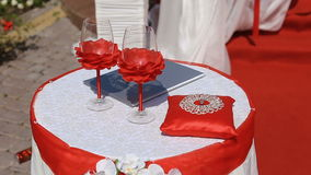 Wineglasses, roses and golden wedding rings on the red atlas pillow.  stock video