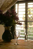 Wineglasses on table. With flowers near window Stock Image