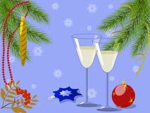 Wineglasses under pine branches. Wineglasses, balls and rowan branch under pine branches, decorated with beads and streamer on a blue background with snowflakes Stock Photo
