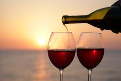 Wineglasses of wine at sunset. Two glasses of red wine at sunset Stock Photo
