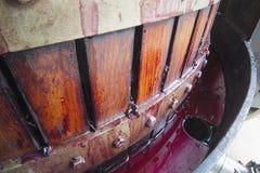 Winegrapes rojos que son machacados en prensa de la cesta Foto de archivo libre de regalías