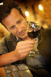 Winegrower tasting a glass of new wine production. Winegrower in wine-cellar holding glass of wine Royalty Free Stock Photo