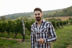Winegrower tasting wine in vineyard Royalty Free Stock Photo
