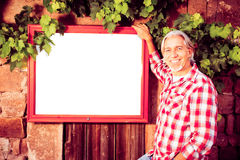 Winemaker With Billboard. Winemaker standing by a billboard. billboard is pure white so you can easily add your own content stock photo