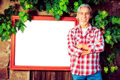 Winemaker With Billboard. Winemaker standing by a billboard. billboard is pure white so you can easily add your own content royalty free stock photo