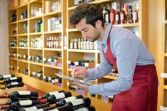 Winemaker in cellar controlling wine market prices on tablet. Man stock photography