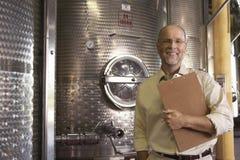 Winemaker With Clipboard Standing nahe bei Gärbottichen Stockbilder
