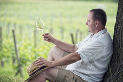 Winemaker drinks white wine. Winemaker tasting a glass white wine in the vineyard Royalty Free Stock Photography