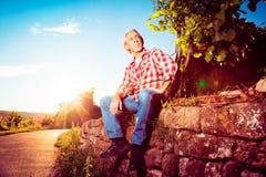 Winemaker-Sitting By His-Weinberg Stockbilder