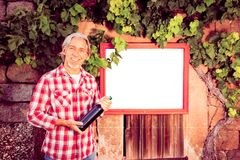 Winemaker With Billboard. Winemaker standing by a billboard. billboard is pure white so you can easily add your own content stock images