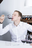Winemaker tasting a red wineglass. Young man on a wine tasting session on the gustatory phase tasting the red wine is writing down in a wine tasting sheet Royalty Free Stock Images