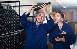 Winemakers человека и женщин с бутылкой вина Стоковые Изображения RF