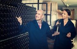 Winemakers человека и женщин с бутылкой вина Стоковые Изображения