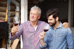 Winemakers at work. Portrait of senior winemaker and young sommelier standing at family winery and tasting red wine. Small business Royalty Free Stock Photo