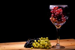 Winemaking. Glass of red wine grapes with green and black bunche. S. Black background with copy space Stock Photo
