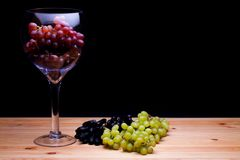 Winemaking. Glass of red wine grapes. White and black grape vari. Winemaking. Glass of red wine grapes. Bunch of white and black grape varieties on farmhouse Royalty Free Stock Images