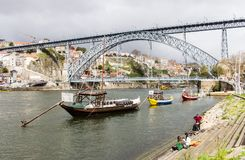 Winery boats moored under Luis I Bridge at Douro river in Porto, Stock Photo