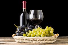 Winery still-life. Varieties of grapes with wineglass and bottle of wine on black background Stock Photo