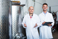 Winery workers standing in fermenting section Stock Image