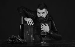 Winetasting and degustation concept. Sommelier leans on wooden chair. Man near glass of wine. Winetasting and degustation concept. Sommelier leans on wooden Royalty Free Stock Image