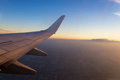 Wing of the air plane on the sea of clouds sunset sky background Royalty Free Stock Photo