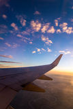 Wing of the air plane on the sea of clouds sunset sky background Royalty Free Stock Image