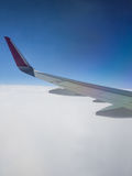 Wing from Aircraft above the clouds Stock Images
