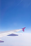 Wing aircraft against a background of blue sky and clouds. The view from the porthole Royalty Free Stock Images