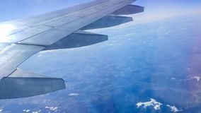 The wing aircraft in altitude during flight. Clouds mountains Stock Images