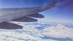 The wing aircraft in altitude during flight. Clouds mountains Stock Photos