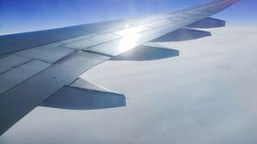 The wing aircraft in altitude during flight. Clouds mountains Stock Photo