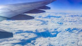 The wing aircraft in altitude during flight. Clouds mountains Royalty Free Stock Image