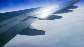 The wing aircraft in altitude during flight. Clouds mountains Stock Photography