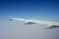Wing of aircraft in flight. With clouds and blue sky background royalty free stock photo