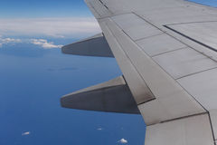 Wing of aircraft flying above sea Royalty Free Stock Photo