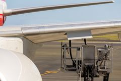 Wing of an aircraft during fuelling. With an elevated motorised platform with rubber pipes parked under an open flap on the apron at an airport in a concept of Royalty Free Stock Image