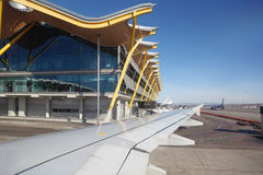Wing of aircraft and Madrid Barajas Airport building Stock Photo