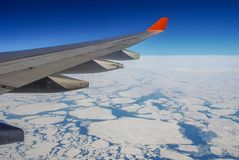 The wing of the aircraft over the Arctic ocean royalty free stock photo